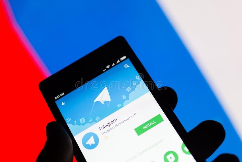 MOSKAU, RUSSLAND - 17. APRIL 2018: Ein Handy in der Hand mit der Telegrammanwendung auf dem Google-Spielspeicher Russische Flagge lizenzfreie stockfotografie