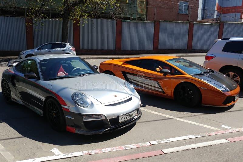 Moskau, Russland - 14. April 2019: exklusives Porsche 911 mit Aerografie und Mansory, das nahe Leuchtorange Lamborghini Gallardo  lizenzfreie stockbilder