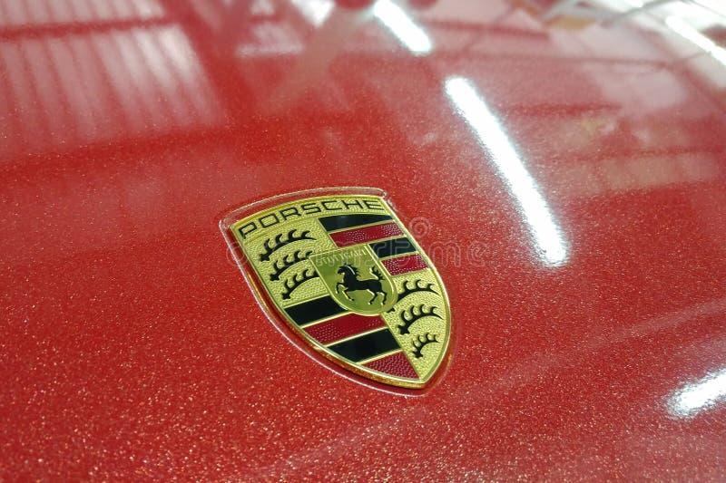 Moskau, Russland - 14. April 2019: Porsche Macan wickelte im hellen roten metallischen Farbvinylfilm ein Logo auf der Haubennahau stockfotos