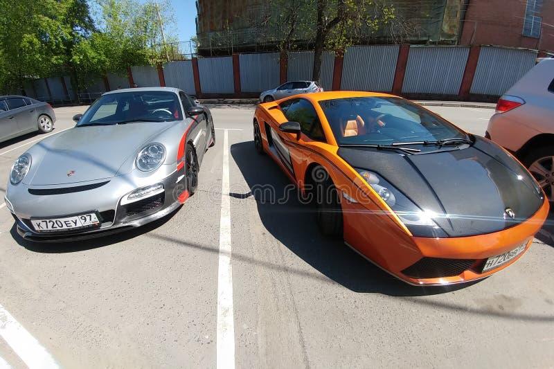 Moskau, Russland - 14. April 2019: Porsche 911 mit Aerografie und Mansory, das nahe Leuchtorange Lamborghini Gallardo mit abstimm stockfoto