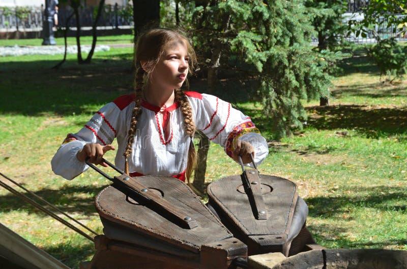 Moskau, Russland, August, 12, 2018 Junges Mädchen in einem Volkskleid bläst den Pelz des Ofens eines alter Schmiedes auf Chistopr lizenzfreies stockfoto