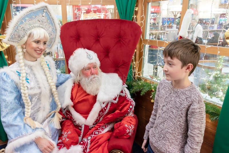MOSKAU, RUSSLAND - 1. DEZEMBER 2018: Ein Junge trifft Sankt in seinem Haus am Weihnachtsabend des Geschäftes der zentrale Kinder, lizenzfreie stockbilder