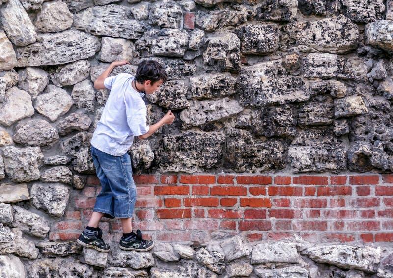 2010 05 30, Moskau, Russland Ein Junge, der auf der Steinwand im des Alexanders Garten von Moskau der Kreml klettert stockbilder