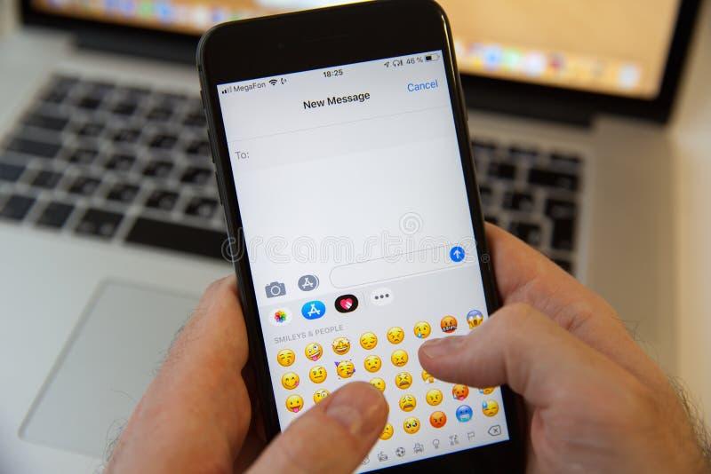 Moskau/Russland - 20. Februar 2019: Schreiben einer neuen Mitteilung auf dem iPhone auf dem Hintergrund MacBooks stockfotografie