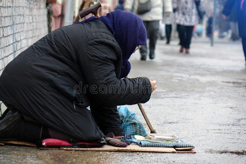 moskau Russland - Januar 2018 Traurige obdachlose Frau, die auf der Obdachlosen vorbei überschreitet sitzt stockfotos