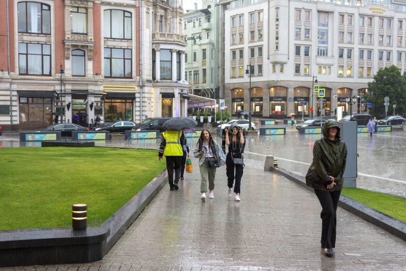 Moskau, Russland, am 17. Juli 2019 Sommerregen in Moskau, Leute ohne Regenschirme gehend hinunter die Straße lizenzfreie stockfotos