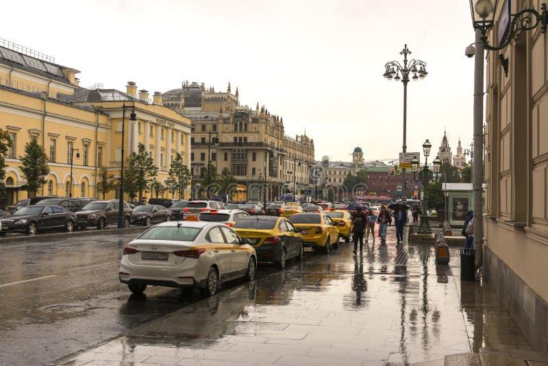 Moskau, Russland, am 17. Juli 2019 Sommerregen in Moskau, Leute unter Regenschirmen gehend hinunter die Straße stockbilder