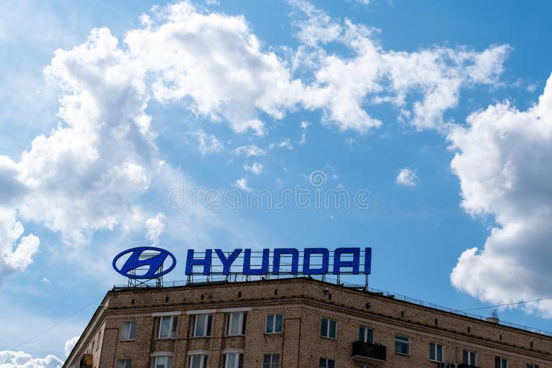 Moskau, Russland - 9. Juli 2019: Werbeschild HYUNDAI auf dem Dach des Stadtgebäudes Hintergrund von Wolken und von blauem Himmel stockfotografie