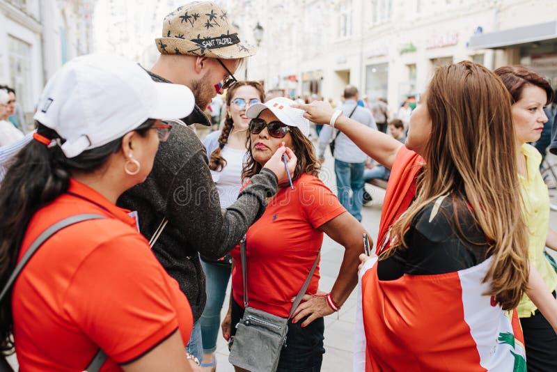 MOSKAU, RUSSLAND - JUNI 2018: Ein Mann zeichnet die Flagge von Peru auf dem Gesicht einer Frau, die in einem roten T-Shirt geklei lizenzfreies stockbild