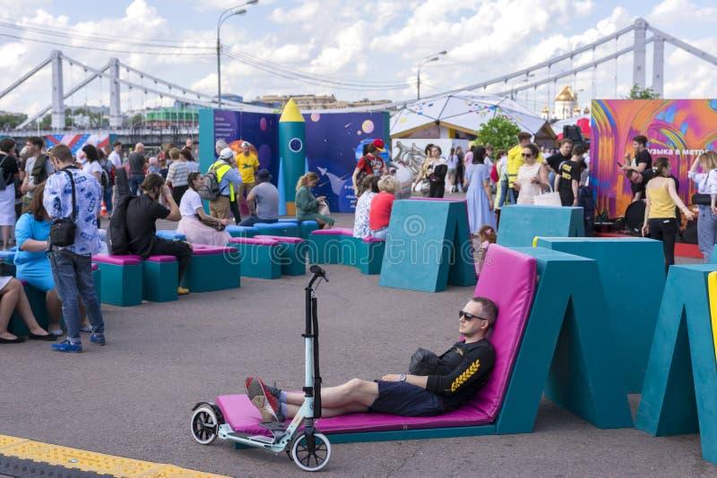Moskau, Russland, am 2. Juni 2019 Genommen auf 31 Ein Mann mit einem Roller, der auf sunbed im Stadt Park stillsteht stockbilder