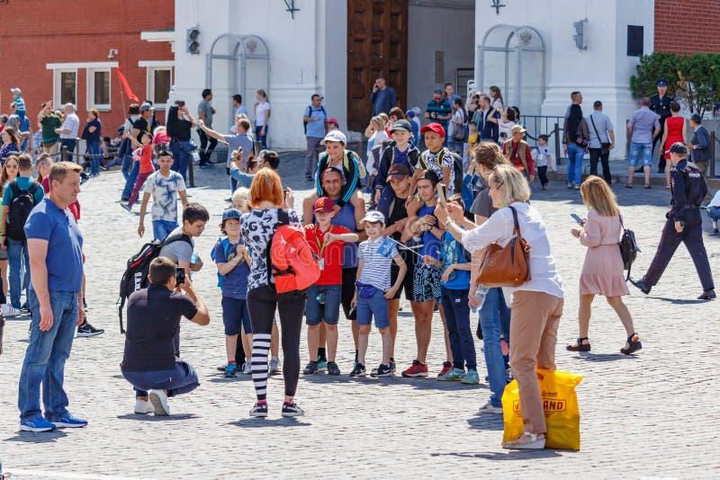 Moskau, Russland - 2. Juni 2019: Gruppe Touristen macht ein Foto auf rotem Quadrat gegen Wand von Moskau der Kreml am sonnigen So lizenzfreie stockbilder
