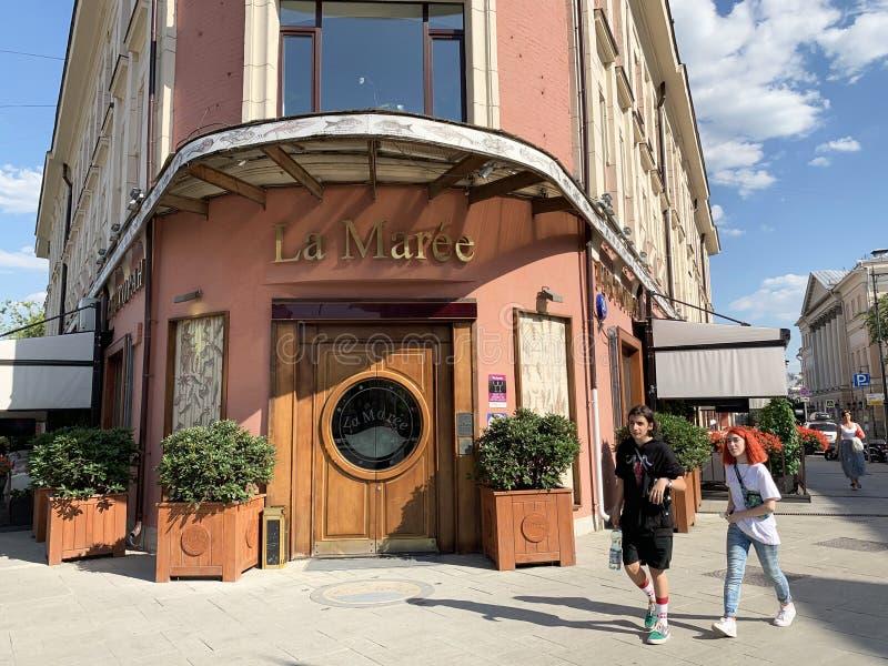 Moskau, Russland, Juni 20, 2019 Junger Kerl und Mädchen vor Restaurant La Maree Früher Apartmenthaus des Vysoko-Petrovsk lizenzfreie stockfotos