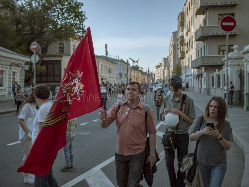 MOSKAU, RUSSLAND - 9. MAI 2016: Mann mit einer roten Fahne und Familie gehen entlang Straße nach dem Marsch Unsterblich-Regiment lizenzfreies stockfoto