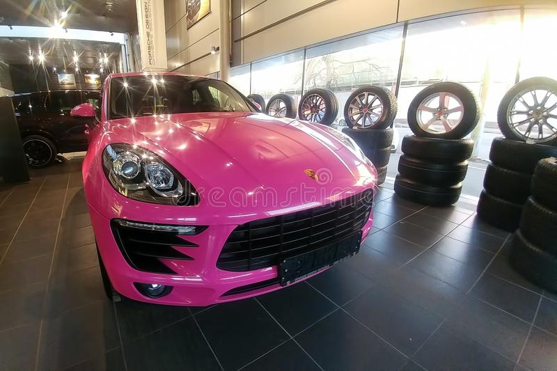 Moskau, Russland - 9. Mai 2019: Rosa Porsche Macan im Ausstellungsraum der H?ndlermitte Auto wird in farbigem sch?tzendem Film ei stockfotografie