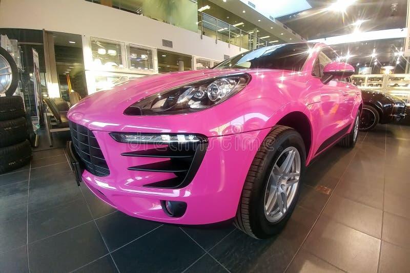 Moskau, Russland - 9. Mai 2019: Rosa Porsche Macan im Ausstellungsraum der H?ndlermitte Auto wird in farbigem sch?tzendem Film ei lizenzfreies stockfoto