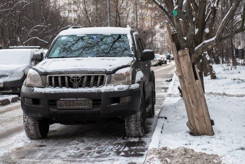 MOSKAU, RUSSLAND, NOVEMBER, 28 2018: Verlassener Schnee bedeckte Auto Toyota Land Cruiser auf einer Großstadtstraße Konsequenzen  stockbild
