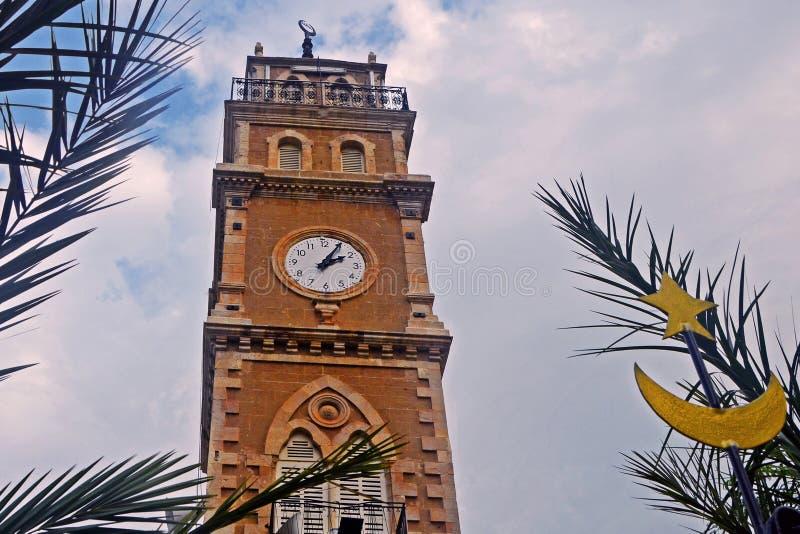 Moskee met een klok tegen een achtergrond van bladeren van palmen en blauwe hemel met wolken in de stad van Haifa in Israël royalty-vrije stock foto