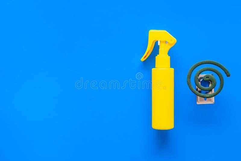 Moskitoschutze Einzelperson und für offenen Raum Grüne Spirale und Spray auf Draufsicht des blauen Hintergrundes kopieren Raum stockfoto
