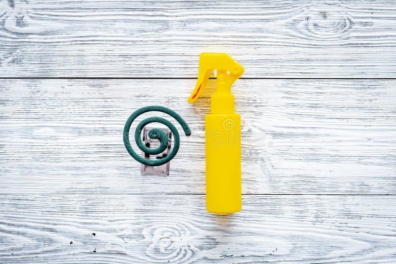 Moskitoschutze Einzelperson und für offenen Raum Grüne Spirale und Spray auf grauem hölzernem Draufsichtraum des Hintergrundes fü stockbilder