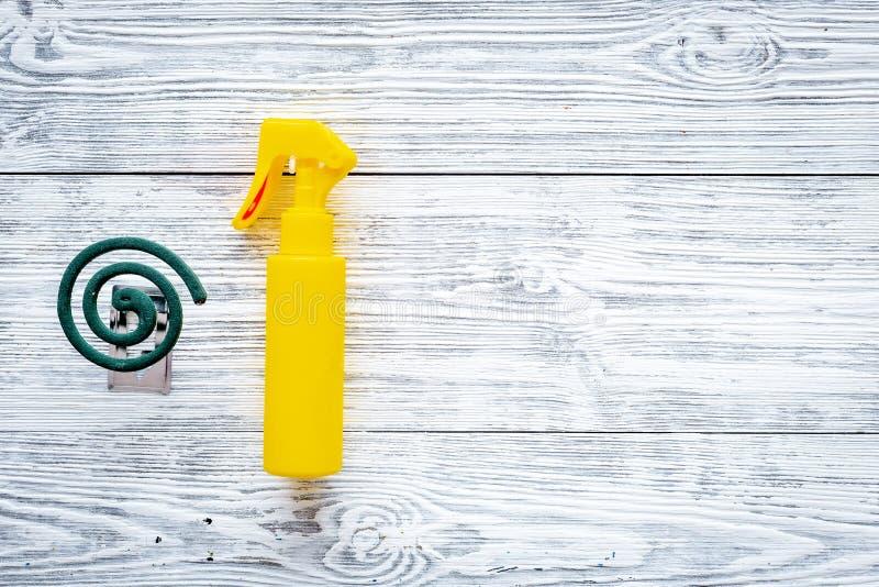 Moskitoschutze Einzelperson und für offenen Raum Grüne Spirale und Spray auf grauem hölzernem Draufsichtraum des Hintergrundes fü stockfoto