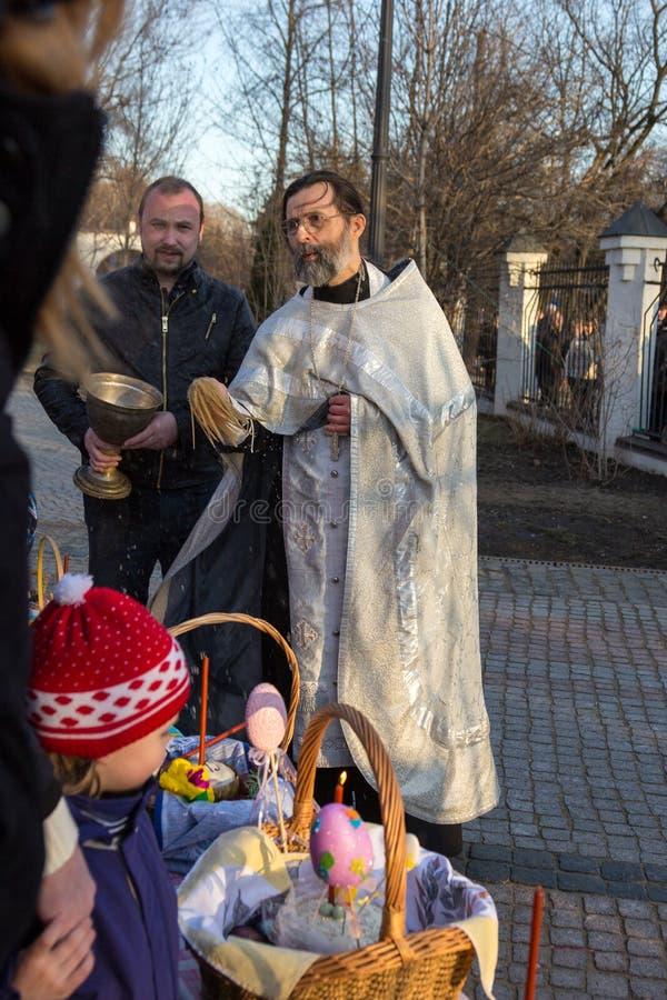MOSKOU - APRIL 11, 2015: De orthodoxe priester bestrooit paaseieren a stock fotografie