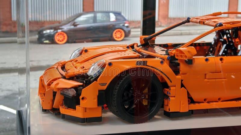 moskou De herfst van 2018 Origineel Lego Porsche 911 Gt3 RS bij het Porsche-handel drijven Lage echte auto met oranje wielen op a royalty-vrije stock afbeeldingen