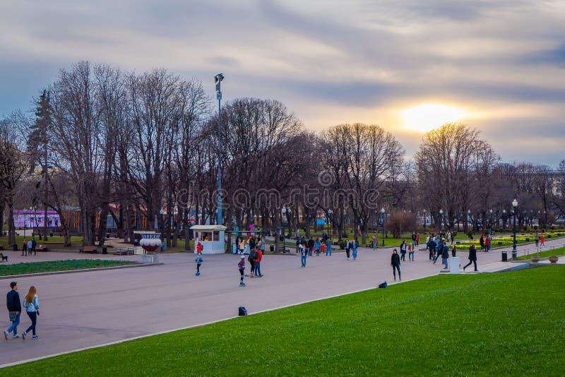 MOSKOU, RUSLAND 24 APRIL, 2018: De openluchtmening van mensen berijdt, schaatst en loopt dichtbij het park van Gorky, die een zon stock foto's