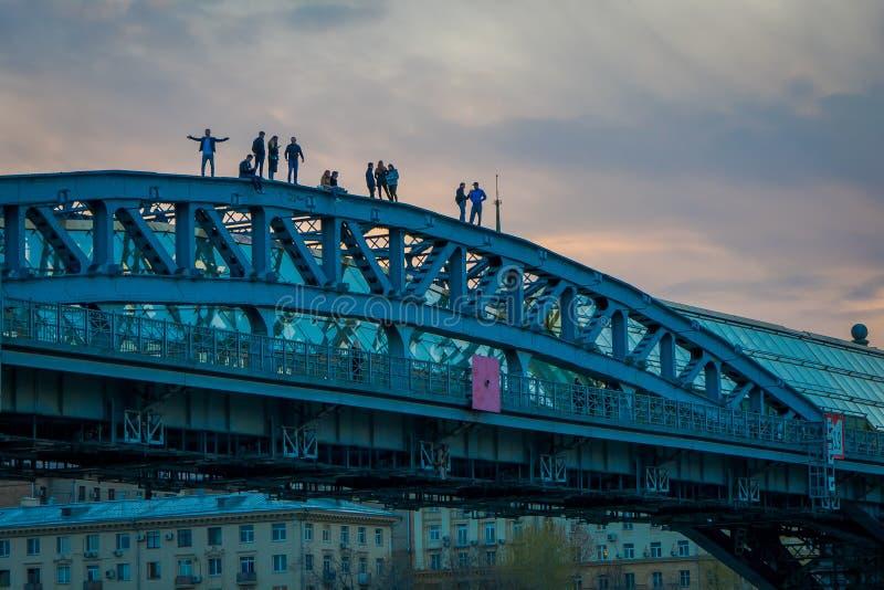 MOSKOU, RUSLAND 24 APRIL, 2018: Niet geïdentificeerde mensen over Andreevsky-Brug voor voetgangers, de de rivierdijk van Moskou stock afbeelding