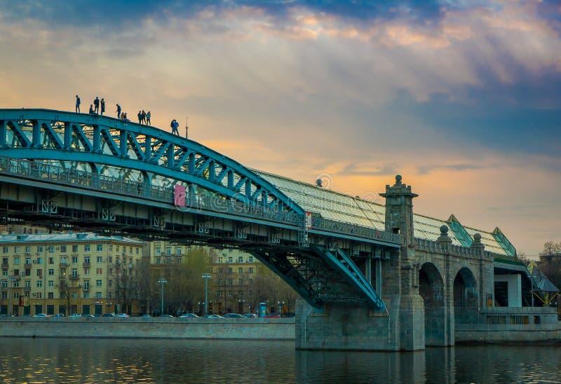 MOSKOU, RUSLAND 24 APRIL, 2018: Niet geïdentificeerde mensen over Andreevsky-Brug voor voetgangers, de de rivierdijk van Moskou stock afbeeldingen
