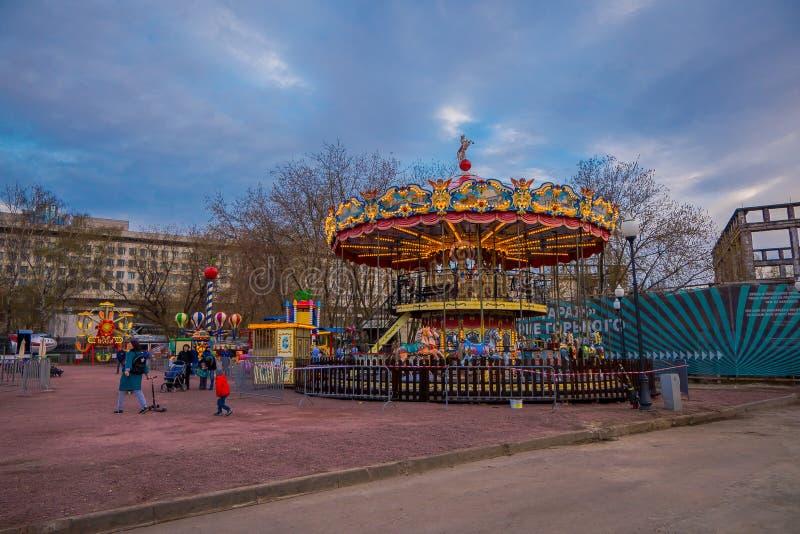 MOSKOU, RUSLAND 24 APRIL, 2018: Openluchtmening van mensen met hun kinderen in een carrousel die van de vrije tijd genieten met royalty-vrije stock afbeelding