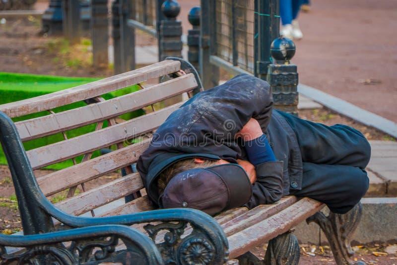 MOSKOU, RUSLAND 29 APRIL, 2018: Openluchtmening van niet geïdentificeerde dakloze mensenslaap als openbare voorzitter in een park stock fotografie