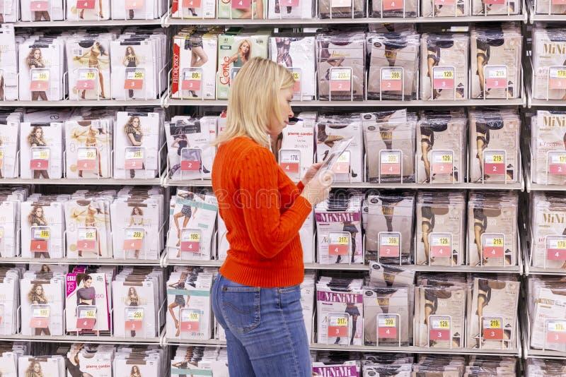 Moskou, Rusland, 11/22/2018 De jonge vrouw in de winkel kiest legging royalty-vrije stock afbeeldingen