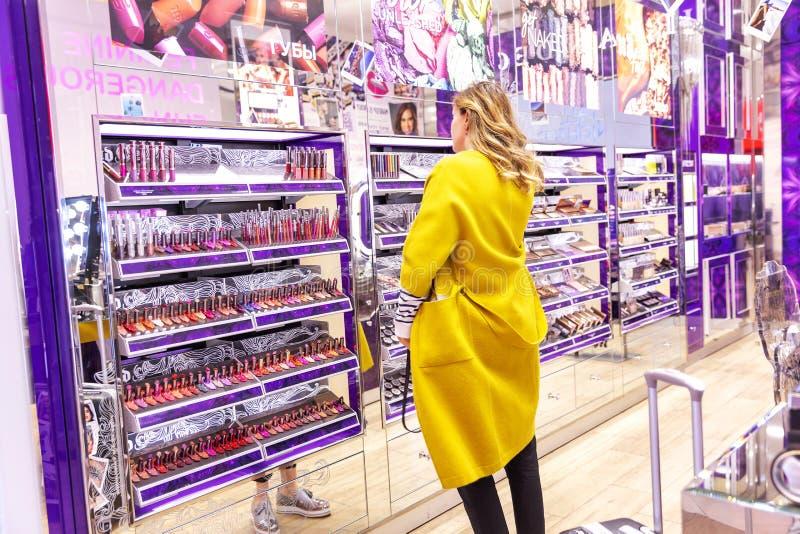 Moskou, Rusland, 10/16/2018: Een jonge vrouw kiest schoonheidsmiddelen in het winkelcentrum royalty-vrije stock foto's
