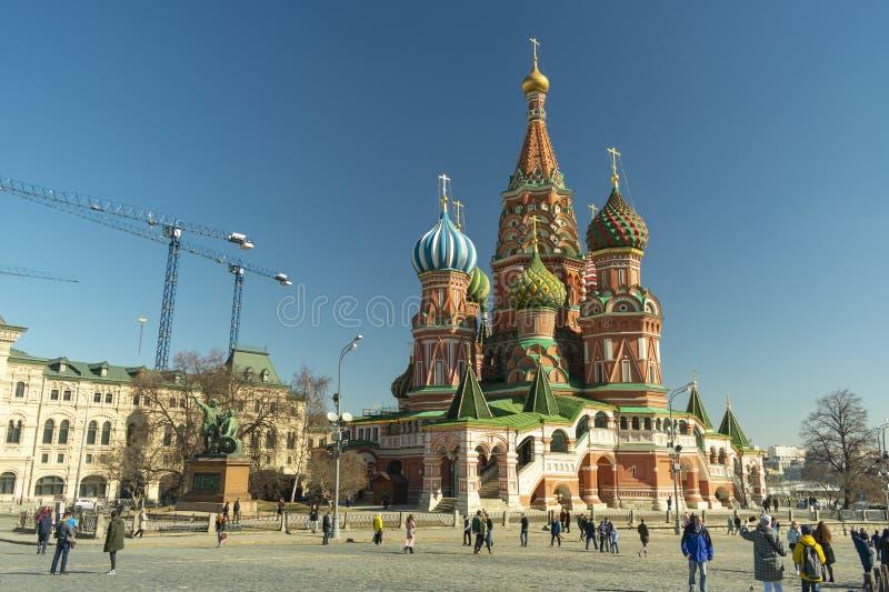 Moskou/Rusland - 04 2019: Het rode vierkant van Moskou, St de Kathedraal van het Basilicum en lopende toeristen stock fotografie