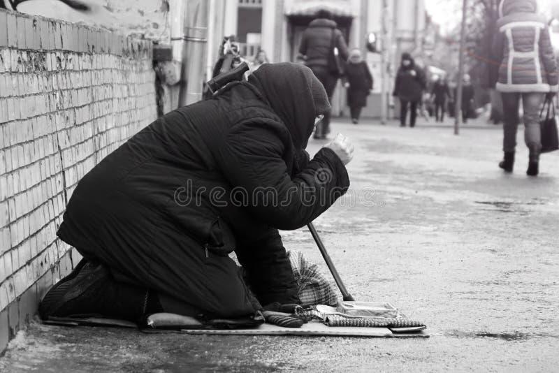 moskou Rusland - Januari 2018 Droevige dakloze vrouwenzitting op de straatmensen die overgaan door Zwart-witte foto royalty-vrije stock fotografie