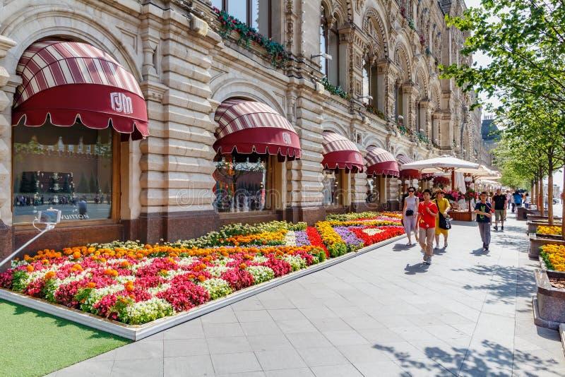 Moskou, Rusland - Juli 28, 2019: Toeristen die op Rood vierkant in Moskou tegen verfraaid door bloemenvoorgevel lopen van GOMstaa royalty-vrije stock fotografie