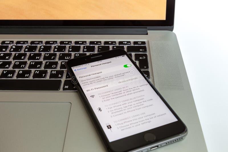 Moskou/Rusland - Juli 10, 2019: Zwart iPhone 8 plus rust op het MacBook-toetsenbord De modem wordt toegelaten op het scherm stock afbeelding