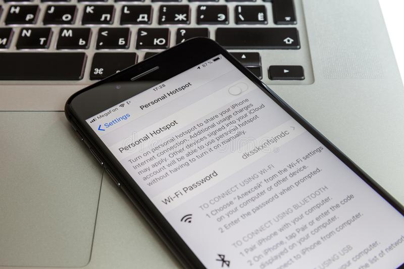 Moskou/Rusland - Juli 10, 2019: Zwart iPhone 8 plus rust op het MacBook-toetsenbord De modem wordt uitgezet op het scherm stock foto