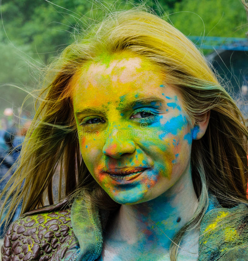 Moskou, Rusland - Juni 3, 2017: Gezicht van jong blondemeisje, behandelde verschillende kleuren door verven Holi bij een kleurrij stock afbeelding