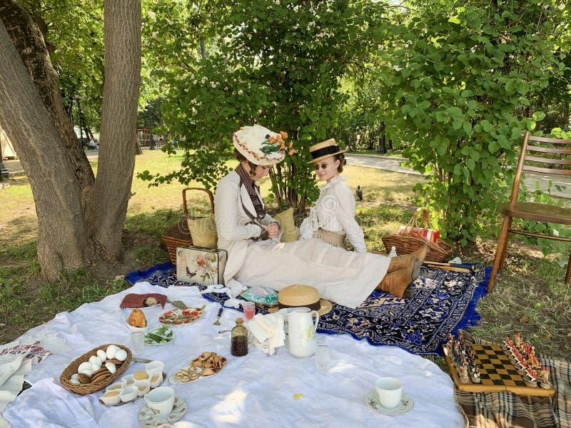 Moskou, Rusland, Juni 20, 2019 Vrouwen in retro kostuums bij een picknick in het park op de vierkante Peter poort van poortpetrov stock afbeelding