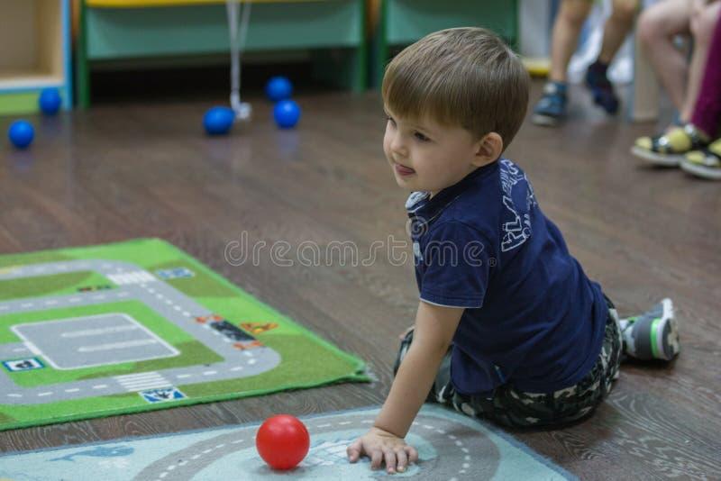 2019 01 22, Moskou, Rusland Leuk weinig jongenszitting op het tapijt in de jong geitjetuin royalty-vrije stock foto