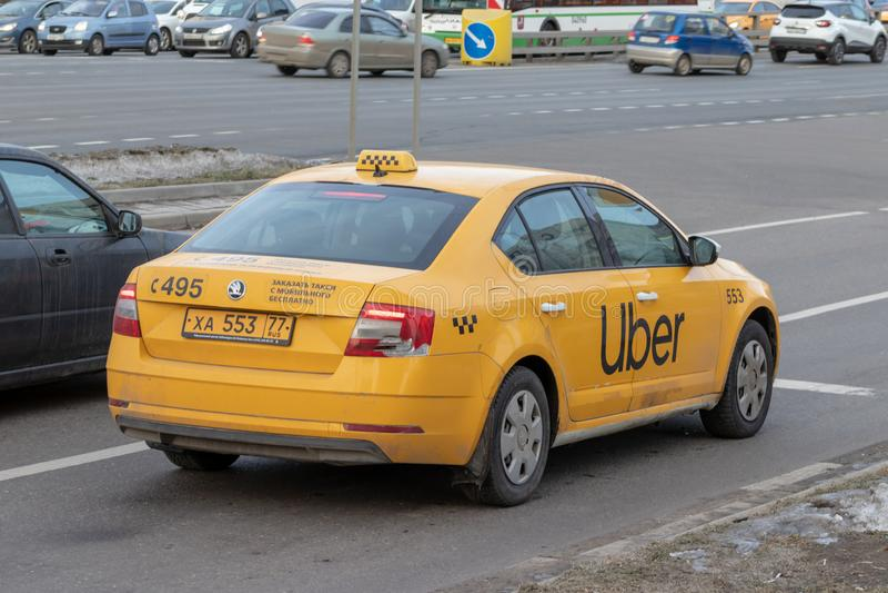 MOSKOU, RUSLAND - MAART 07, 2019: Nieuwe gele stadstaxi met uberembleem op het zij berijden langs de straat stock foto