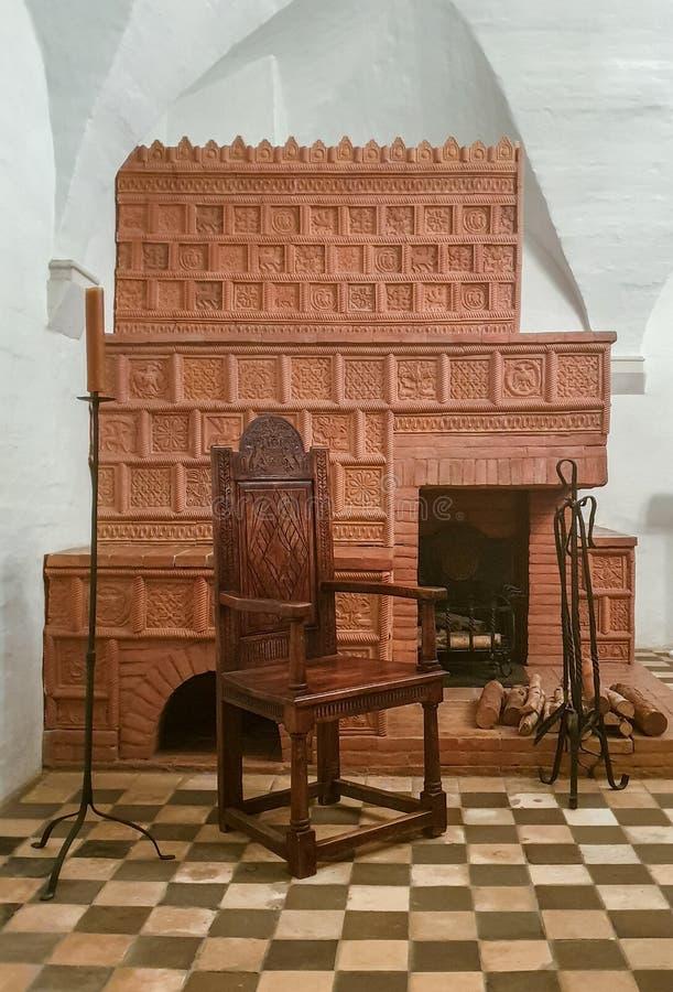 moskou Rusland - Mei 12, 2019: authentiek historisch middeleeuws binnenland met een houten stoel, kaarsen en een open haard met t stock fotografie