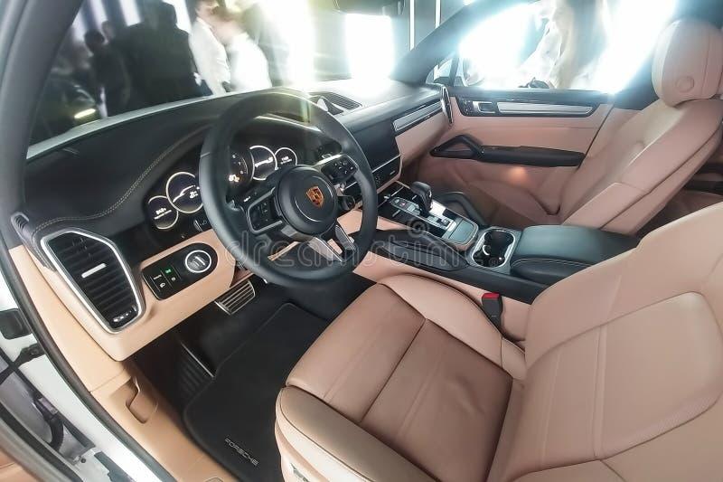 Moskou, Rusland - Mei 09, 2019: Beige en zwart luxebinnenland van volledig nieuw Wit Porsche Cayenne in een presentatievakje stock afbeelding