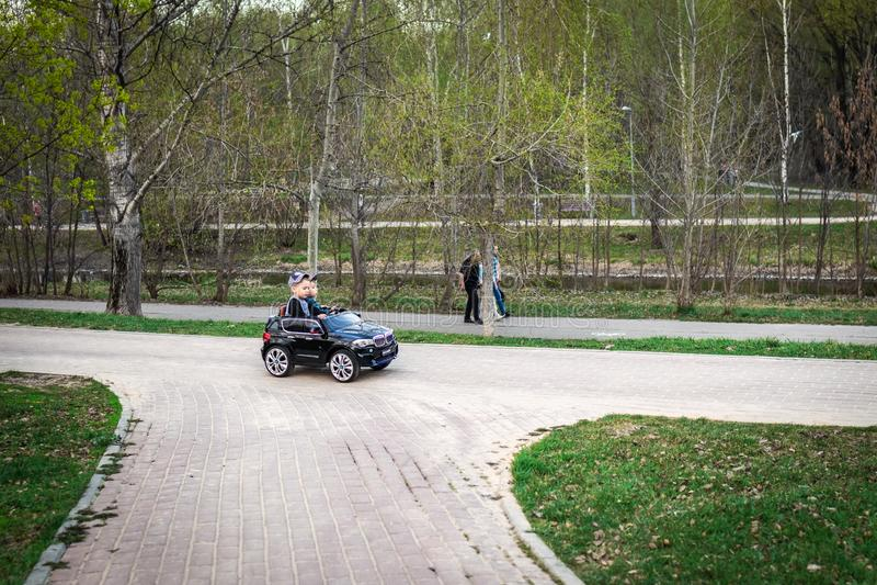 MOSKOU, RUSLAND - MEI 1, 2019: De grappige bestuurder van de jongensauto met het stuurwiel ??njarigenjongen in een wit overhemd i royalty-vrije stock fotografie