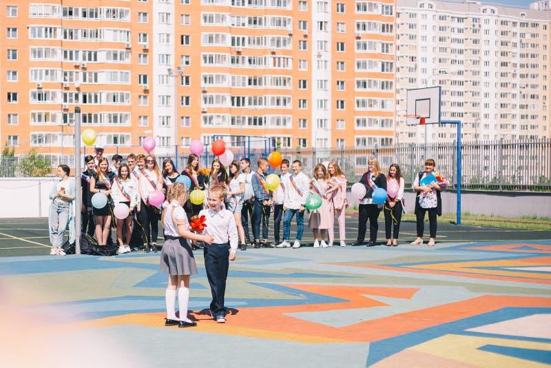 Moskou, Rusland - 22 Mei 2019: Het de schoolkinderenjongen en meisje bellen de klok op de laatste klok en de graduatie stock foto's