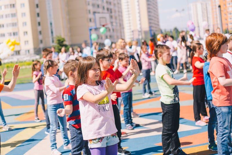 Moskou, Rusland - 22 Mei 2019: Kinderen die op school op een vakantie in het schoolplein dansen Nadruk op meisje stock foto