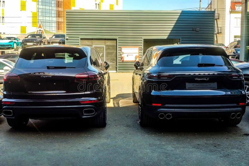 Moskou, Rusland - Mei 18, 2019: Nieuwe en oude generatie van Porsche Cayenne in grijs-blauwe kleur dat op de straat wordt geparke stock fotografie