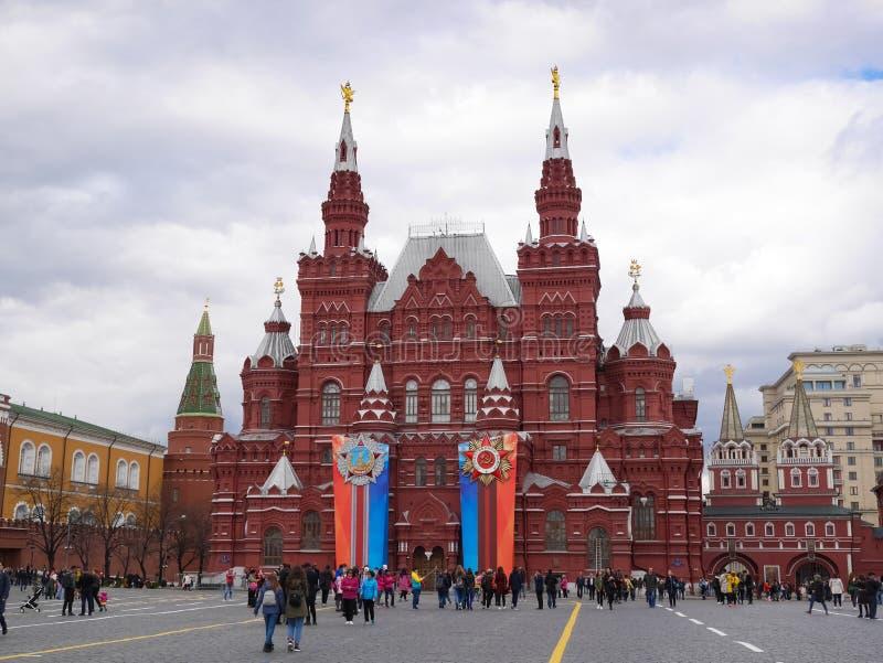 Moskou, Rusland Mensen die dichtbij het Historische die Museum SHM lopen van de Staat met Kentekens ter ere van Victory Day On Re royalty-vrije stock foto