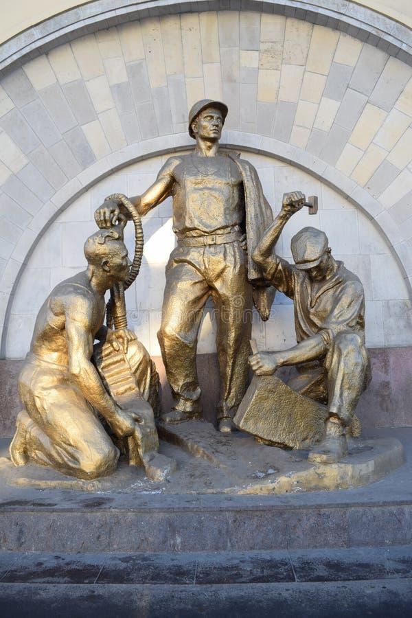 MOSKOU, RUSLAND - NOVEMBER 28, 2015: Het beeldhouwwerk van metro bouwers stock afbeelding
